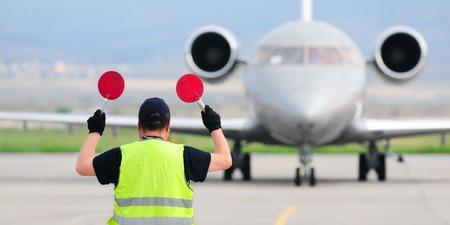 Controlador de tránsito aéreo con carteles en el aeropuerto