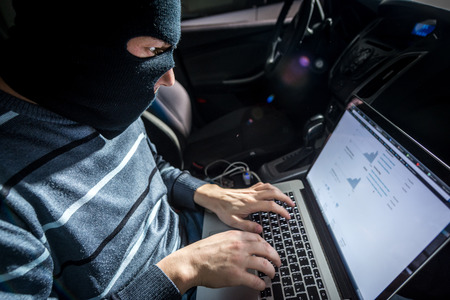 Hacker in a mask with a laptop inside a car