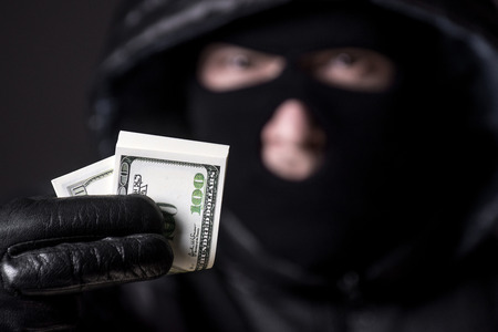 Bandit in a mask holding the money Stock Photo