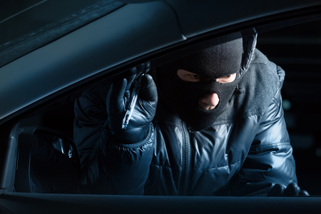 looking inside: Car robber at night looking inside a car