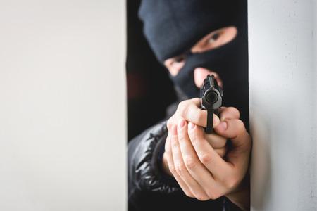 murderer: Murderer in a mask with an aiming black gun