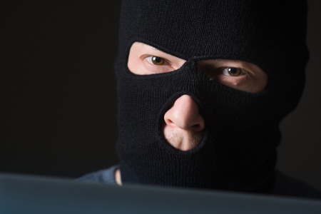 crime: Terrorist in a mask using computer for crime