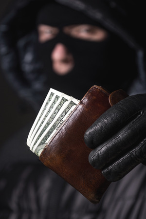 hijack: Bandit in a mask holding the money Stock Photo