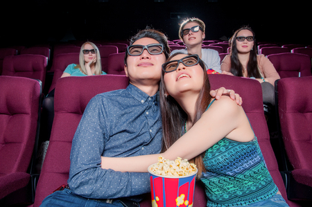woman in love: People in the cinema wearing 3d glasses and watching movie