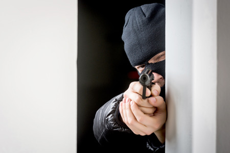 Murderer in a mask with an aiming black gun