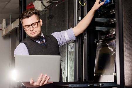 young engineer: Young engineer wearing glasses in a datacenter
