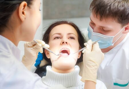 examined: Female patient with open mouth examined by a dentist
