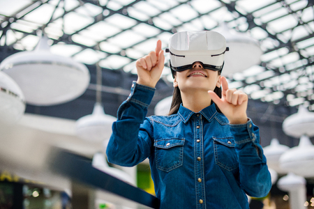 Emotional pretty woman wearing virtual reality glasses Foto de archivo