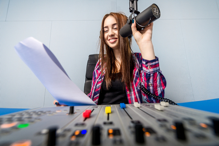 newsreader: female dj working in front of a microphone on the radio