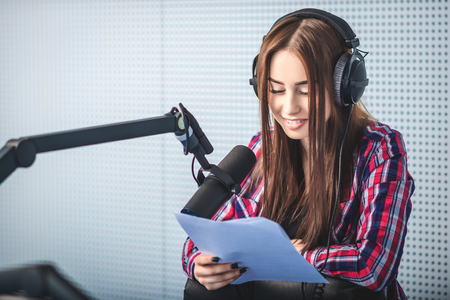 female dj working in front of a microphone on the radio Imagens - 57601702