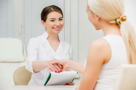 ilness: Doctor talking to her female patient at office