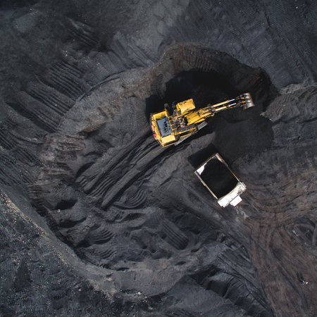 resourse: Top view of an excavator loading the truck with coal Stock Photo