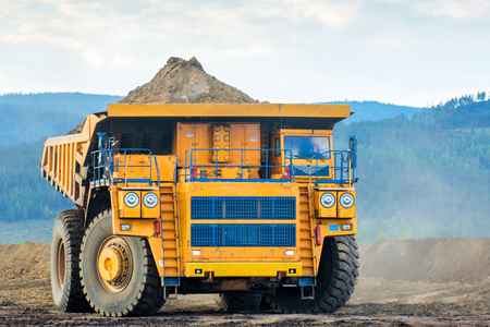 Big yellow mining truck ground moving in open pit