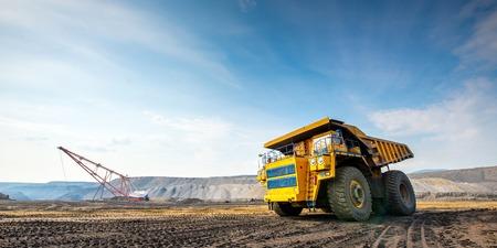 Gran fondo amarillo carro de mina a cielo abierto que se mueve en Foto de archivo