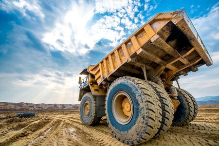 Grote gele mijnbouwvrachtwagen grond bewegen in open pit Stockfoto