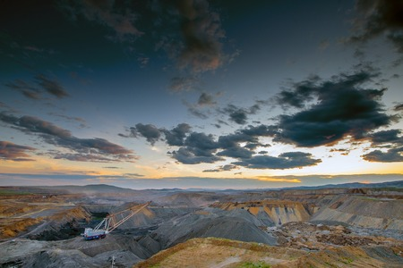dragline: Coal mining in open pit at the sunset.