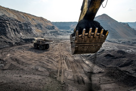 coal truck: An excavator loading big truck with coal in open pit