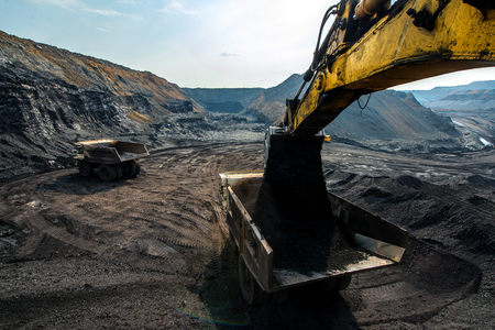 open pit: An excavator loading big truck with coal in open pit