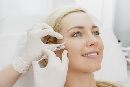 Beautiful woman gets beauty facial injections. Face aging injection. Aesthetic Cosmetology Stock Photo