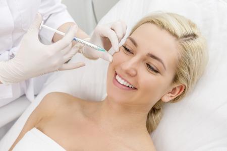 美しい女性は、美しさの顔注射を取得します。射出高齢化に直面します。審美的な美容