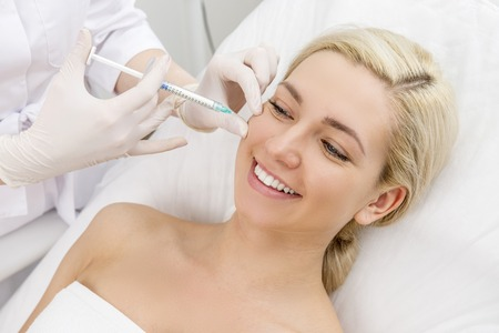 Beautiful woman gets beauty facial injections. Face aging injection. Aesthetic Cosmetology Foto de archivo