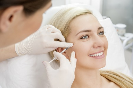 aging woman: Beautiful woman gets beauty facial injections. Face aging injection. Aesthetic Cosmetology Stock Photo