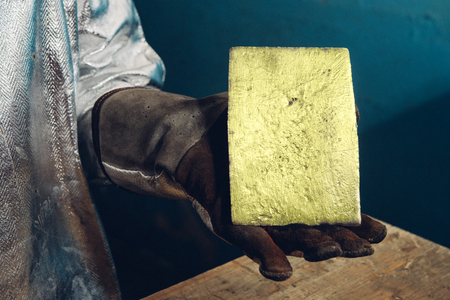 raw gold: Raw gold ingot in hands just made at a factory