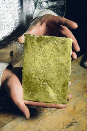 gold ingot: Raw gold ingot in hands just made at a factory
