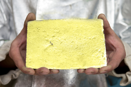 ingot: Raw gold ingot in hands just made at a factory