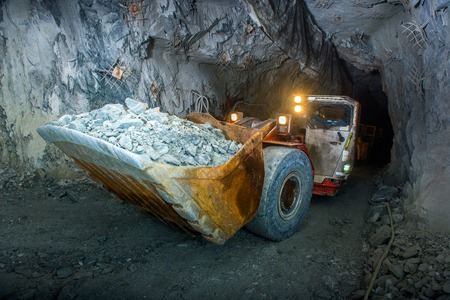 Working inside gold mine tunnel. Gold mining. Stock Photo