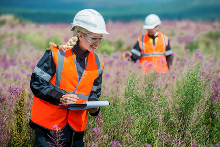 metodo cientifico: Man and woman researching recultivated field in russia Foto de archivo