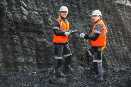 open pit: Two speacialists examining coal at an open pit