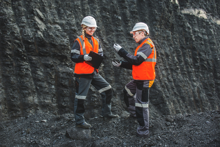 engeneer: Two speacialists examining coal at an open pit