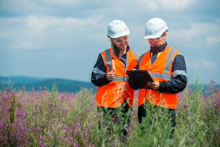 Man and woman researching recultivated field in russia Editorial