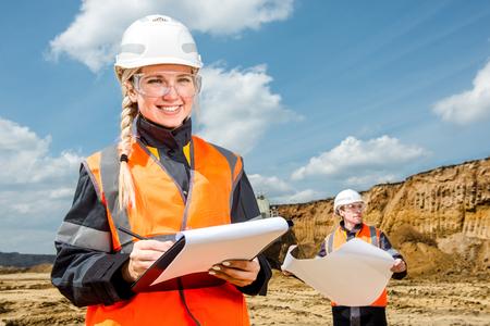 topografo: Mujer y un hombre que trabaja en un proyecto en una mina a cielo abierto