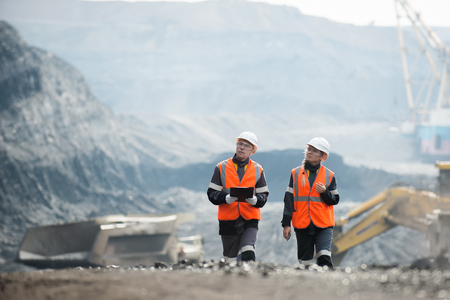 Two speacialists examining coal at an open pit