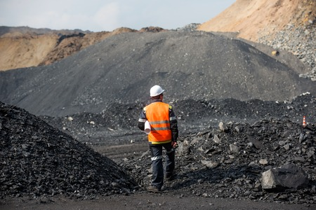 Coal mining in an open pit - Worker is looking on the huge open pit Standard-Bild