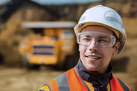 Trabajador de mina con un enorme camión en el fondo de cielo abierto
