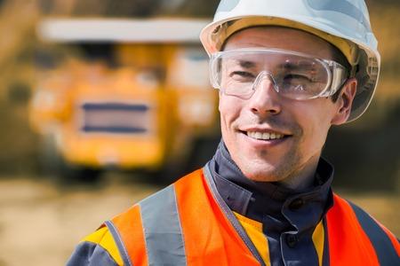 Trabajador de mina con un enorme camión en el fondo de cielo abierto Foto de archivo