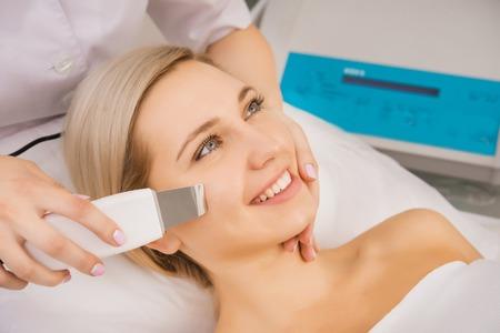 Young beautiful woman applying ultrasound facial skin peeling