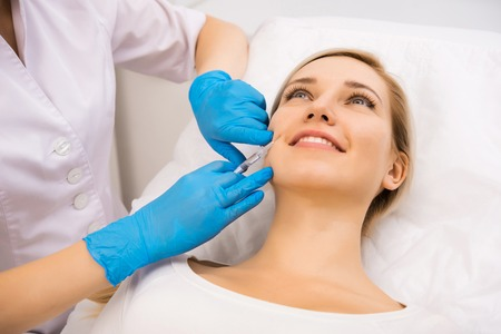 aging face: Beautiful woman gets beauty facial injections. Face aging injection. Aesthetic Cosmetology Stock Photo