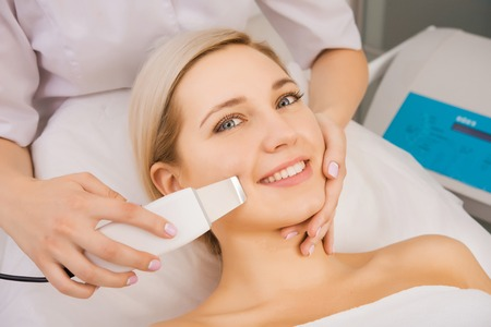 massager: Young beautiful woman applying ultrasound facial skin peeling