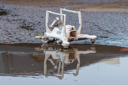 risky innovation: Crashed quadcopter after an accident laying on the ground