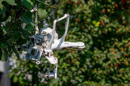 Crashed quadcopter after an accident hanging on a tree