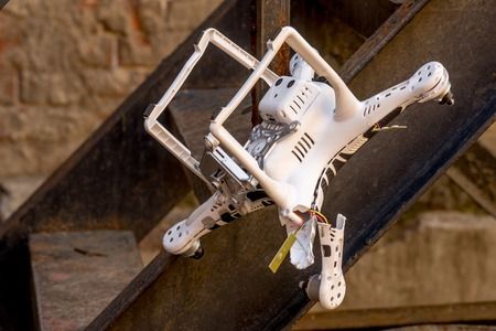 risky innovation: Crashed quadcopter after an accident that stuck on the ladder