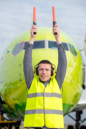 air traffic: air traffic controller holding light signs at the airport Stock Photo
