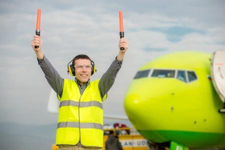Contrôleur de la circulation aérienne tenant des signes de lumière à l'aéroport Banque d'images - 63875909