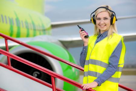 Ingegnere aeronautico con radio CB in piedi di fronte a un aereo di linea commerciale Archivio Fotografico - 63876129