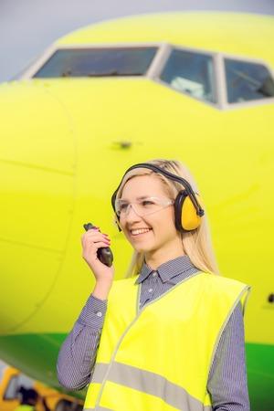 overol: ingeniero de los aviones con la radio CB de pie delante de un avión comercial