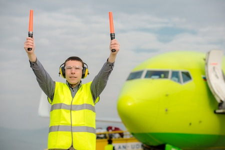 air traffic controller holding light signs at the airport Standard-Bild